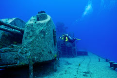 Divers exploring a shipwreck. A diver explores the huge gun that sits atop the superstructure of the sunken wreck, the Tibbetts, a Russian frigate that was sunk Stock Photo
