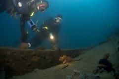Divers exploring a wreck, Croatia. Divers exploring a wreck and a small scorpionfish, Croatia Stock Images