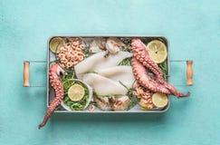 Divers fruits de mer dans le plateau : poulpe, crevette, calmar et algue sur le fond bleu-clair photo stock