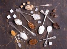 Divers genres de sucre dans de vieilles cuill?res sur le fond en bois fonc? photographie stock libre de droits