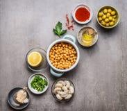 Divers ingrédients à cuire dans des cuvettes pour la salade de pois chiche sur le fond concret gris, vue supérieure Photos libres de droits