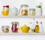 Divers ingrédients et ustensiles de nourriture sur des étagères de cuisine d'isolement Images libres de droits