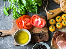 Divers ingrédients frais pour faire des sandwichs - légumes - tomates et arugula, pain, prosciutto, huile d'olive sur l'obscurité photos libres de droits