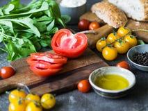 Divers ingrédients frais pour faire les sandwichs - formage de légumes, de pain, d'huile d'olive et caillé sur le fond foncé photos stock
