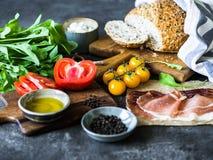 Divers ingrédients frais pour faire les sandwichs - formage de légumes, de pain, de prosciutto, d'huile d'olive et caillé sur le  images stock