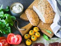Divers ingrédients frais pour faire les sandwichs - formage de légumes, de pain, de prosciutto, d'huile d'olive et caillé sur le  images libres de droits