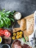 Divers ingrédients frais pour faire les sandwichs - formage de légumes, de pain, de prosciutto, d'huile d'olive et caillé sur le  photo libre de droits