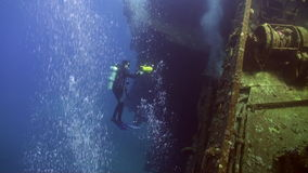 Divers near wreck ship underwater on coral reef Abu Nuhas in Red sea. Swimming in world of colorful beautiful wildlife of fish and algae. Inhabitants in search stock video footage