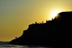 Divers on Ocean Cliff at Sunset Royalty Free Stock Photography
