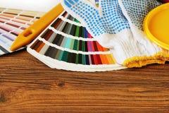 Divers outils, accessoires et échantillons de peinture de couleur pour la rénovation à la maison sur le fond en bois photo stock
