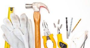 Divers outils de construction D'isolement sur le fond blanc Marteau de DIY, gants et verres de sûreté faits maison, mètre, pinces images libres de droits