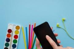 Divers papeterie et téléphone sur le fond bleu photos stock