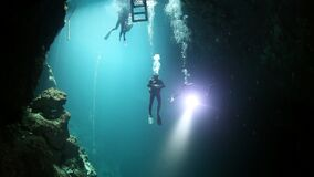 Divers in rocks of underwater cave Yucatan Mexico cenotes.