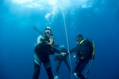 Divers on safetystop on buoy, Croatia. Divers on safetystop on buoy. Croatia Stock Photo