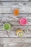 Divers smoothies colorés de fruit dans des bouteilles en verre Images stock