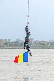 Divers training on the rope near water. Romanian flag. Royalty Free Stock Photography