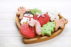 Divers types de biscuits décoratifs de pain d'épice de Noël de plat en forme de coeur en bois sur la vue supérieure blanche de ta Photographie stock libre de droits