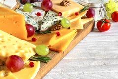 Divers types de fromage avec des raisins, le romarin, les tomates et la grenade sur la planche à découper en bois Image stock