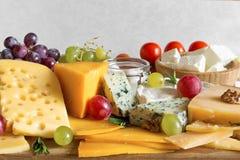 Divers types de fromage sur la planche à découper en bois sur la table en bois rustique avec des raisins, les tomates et le romar Photographie stock