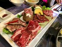 Divers types de viande coupés en tranches minces, champignons et légumes d'un plat blanc, préparé pour le barbecue coréen images stock