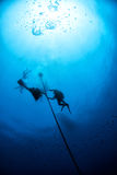 Divers under boat for deco time in the blue Royalty Free Stock Image