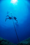 Divers under boat for deco time in the blue Royalty Free Stock Images