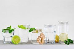 Divers verres de l'eau minérale avec la chaux, le citron, le gingembre et le MI Image libre de droits