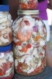 Divers voedsel in azijn - zeevruchten in glasflessen voor verkoop bij een marktkraam royalty-vrije stock foto