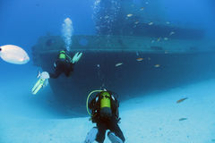 Divers and Wreck. Scuba divers swims to a shipwreck Royalty Free Stock Image