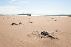 Diversa basura en la costa arenosa lanzada olas oceánicas Arena amarilla y cielo azul foco hacia números más inferiores y medios Foto de archivo