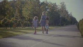 Diversa famiglia con i bambini che fanno una passeggiata in parco archivi video