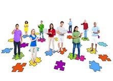 Diversa gente che per mezzo dei dispositivi di Digital con i pezzi del puzzle Immagini Stock