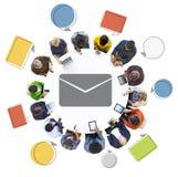 Diversa gente che per mezzo dei dispositivi di Digital con l'icona del email Immagini Stock