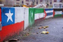 Diversa pintada de las banderas en la pared Imagen de archivo