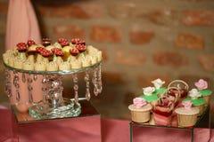 Diversa torta cristalina embellecida dos se coloca de exhibición de una variedad de magdalenas y de tortas mordedura-clasificadas imagen de archivo
