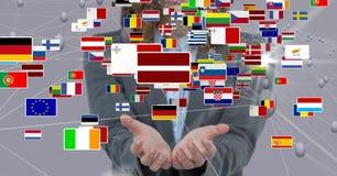 Diversas banderas sobre las manos foto de archivo