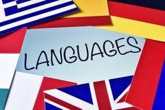 Diversas banderas y las idiomas de palabra en la pantalla de una tableta Foto de archivo libre de regalías