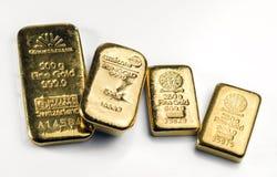 Diversas barras do molde do ouro de pesos diferentes e de fabricantes diferentes encontram-se em uma superfície branca foto de stock royalty free