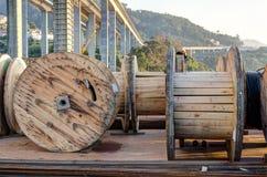 Diversas bobinas de madeira grandes de prestressing os fios de aço sobre uma placa de aço e as barras do reforço com uma ponte co fotos de stock royalty free