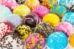 Diversas bolas coloridas de la torta con decorativo asperjan Fotografía de archivo