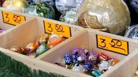 Diversas bolas y juguetes hermosos de la Navidad para adornar el abeto de la Navidad en el contador del mercado Inscripción en al almacen de metraje de vídeo