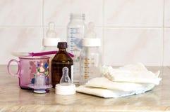 Diversas botellas de cristal con una mezcla de alimentación y de diape del bebé Fotografía de archivo libre de regalías