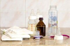Diversas botellas de cristal con una mezcla de alimentación y de diape del bebé Foto de archivo libre de regalías