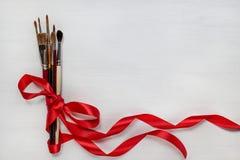 Diversas brochas de la acuarela con la cinta roja Foto de archivo