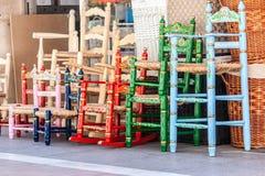 Diversas cadeiras de madeira e de vime em cores diferentes Foto de Stock