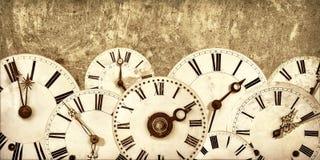 Diversas caras de reloj del vintage delante de una pared vieja Fotografía de archivo