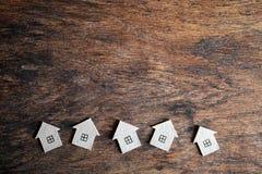 Diversas casas do cartão em um fundo de madeira Imagens de Stock