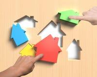 Diversas casas se adaptan al tablero de los agujeros de la forma de la casa con el assembl de las manos Imagen de archivo