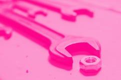 Diversas chaves e parafuso-porca no fundo pintado do metal Rosa tonificado Conceito do feminismo imagens de stock
