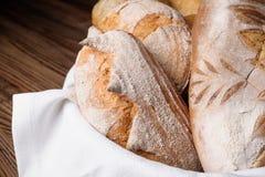 Diversas clases de pan y de baguettes en una cesta de mimbre en una tabla de madera Fotos de archivo libres de regalías